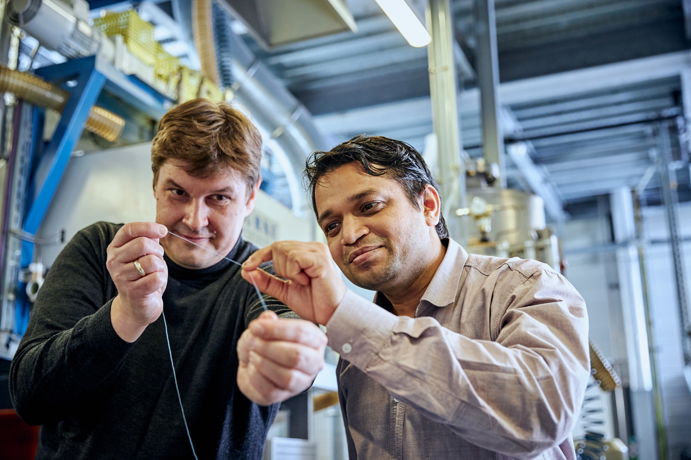 Scientist Pavan Manvi from RWTH Aachen University (right) and Covestro researcher Dr. Jochen Norwig holding a synthetic fibre prototype made from CO2. (Source: Covestro)