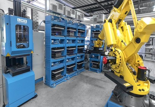 Heating/pressing modules for holding cavity plate sets which, after cavity filling in the injection moulding machine (on the left side of above photo), are transferred there by a robot and then passed on to a demoulding station. (Source: LWB-Automation)