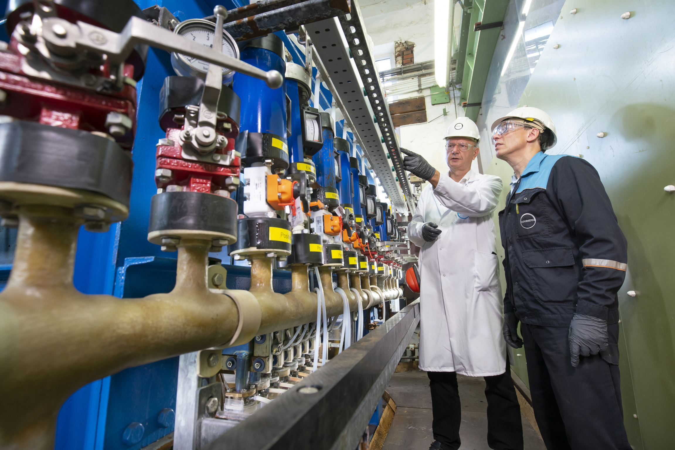 Two Covestro employees inspect a demonstration plant during a planned downtime in Leverkusen, Germany. (Source: Covestro)
